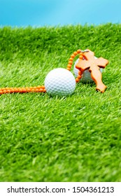 Christian cross are on green grass with golf ball.