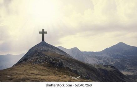 Christian cross on top of the hill with sunrays, crucifixion, religious concept