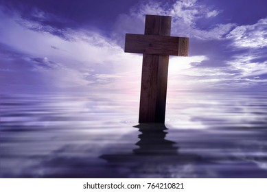Christian cross with reflected on the water over dramatic sky background