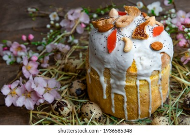 Christian Easter pastries on a wooden background. Panetone decorated with white glaze. Spring flowers on the background of Easter cake