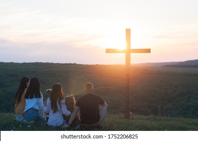 Christian family. Cross. Happy family on the nature.  Children husband and wife. Wooden cross against the sky. Sunset. Summer