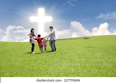 Christian family enjoying their Easter holiday in the park under bright Cross sign