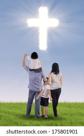 Christian family having fun on green field with cross symbol