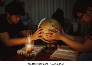 christian family  hold on the blurred world globe and praying together  with a vintage lamp on wooden table in home at night , prayer for the world mission  concept