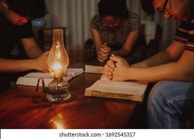 christian family  praying together on blurred bible  with a vintage lamp on wooden table in home at night , devotional or prayer meeting concept