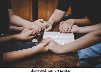 Christian family worship God in home with holy bible on wooden table