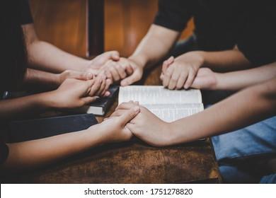 Christliche Familie verehrt Gott zu Hause mit heiliger Bibel auf Holztisch