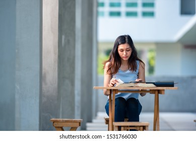 A Christian female is reading the big book of Bible with clam and happy.