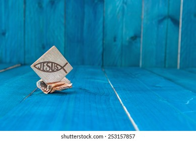 Christian fish symbol carved in wood on white vintage wooden background