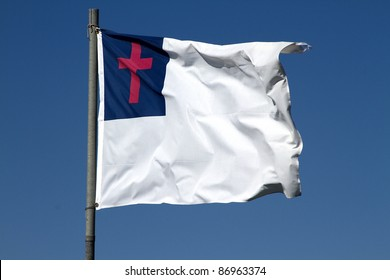 Christian flag with cross flying strong on windy day