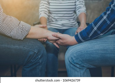 christian friends holding hands and praying togehter indoor