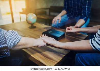 Christian friends holding hands together surrounded wooden table with blurred bible and world globe, christian prayer for world mission concept