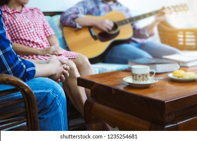 Christian friends praying to God while another person  and plays guitar at home, Christian family, small group or house church worship concept