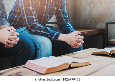 Christian friends sitting on wooden chair while praying together  with holy bible on wood table