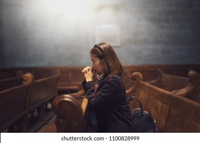 A Christian girl is sitting and praying with humble heart in the church.