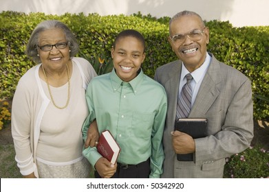 Christian Grandparents and Grandson in garden holding Bibles, portrait