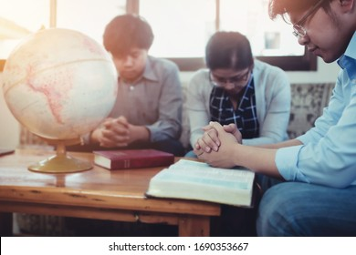 Christian group pray together with  blurred world globe and bible on wooden table , Christian background for prayer ministry for the world and corona virus concept
