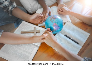 Christian group praying for globe and people around the world on wooden table with bible.