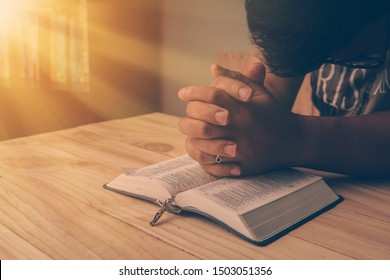 Christian hand while praying and worship for christian religion with blurred of her body background, Casual man praying with her hands together over a closed Bible. christian background. freedom.