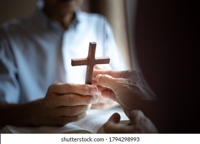 Christian hands of giving cross wood together . Christian good news concept.