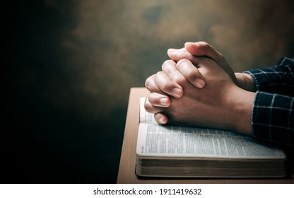 Christian life crisis prayer to god. Man Pray for god blessing to wishing have a better life. man hands praying to god with the bible. believe in goodness. Holding hands in prayer on a wooden table.