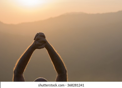 A Christian man praying to God with raised hands at the sunset in the mountains.