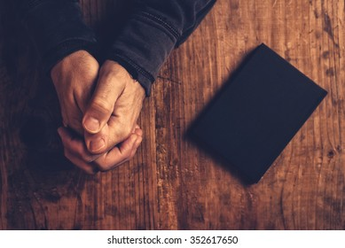 Christian man praying with hands crossed and Holy Bible by his side on wooden desk in church, top view
