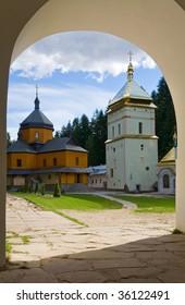 Christian monastery courtyard view through a gate arch (Manjava village, Ivano-Frankivsk Region, Ukraine)
