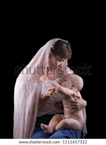 Christian mother with her baby isolated on a black background.