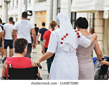 Christian nun walking down the street and helping woman in wheelchair