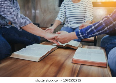 Christian people prays together around wooden table with opened blurred page bible. prayer and bible study group concept.