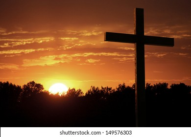 Christian Photo illustration of a Dramatic Sky with Large wooden Cross standing against very saturated colors of bright yellow sun, rich orange clouds, sunlight shafts, and silhouetted trees.