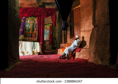 Christian priest keeps the interior of a Christian church in Lalibela in August 2014 Interior of a Lalibela church in Ethiopia where believers perform their prayers and offerings.