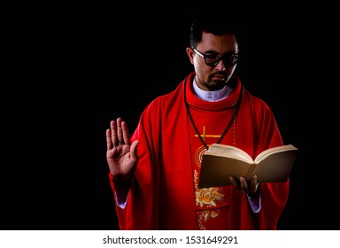 Christian priest is reading bible with black background