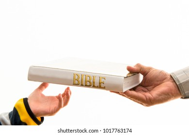 Christian religion: passing the faith to our children. Adult hand gives a Bible to a child.