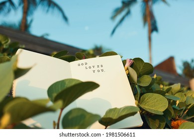 Christian saying 'God loves you' printed with stamps and ink in a diary. Motivational supportive text for religious people in a notebook surrounded by tropical nature, palm trees and greenery