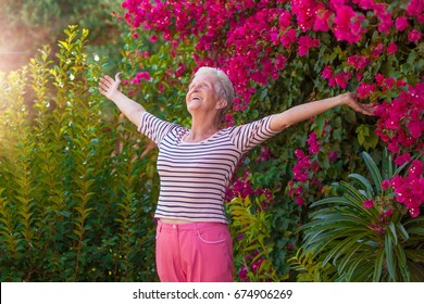Christian senior woman arms outstretched with praise and joy