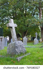 Christian stone cross on a tomb, on a cemetery with grass and trees. Dartmoor, England.