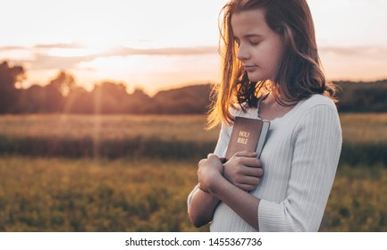 Christian teenage girl holds bible in her hands. Reading the Holy Bible in a field during beautiful sunset. Concept for faith, spirituality and religion. Peace, hope - Shutterstock ID 1455367736