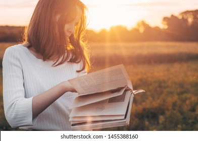 Christian teenage girl holds book in her hands. Reading the book in a field during beautiful sunset. The girl sitting on a grass, reading a book. Rest and reading