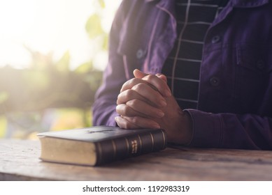 Christian woman holding hands and praying with bible,Pleading to God, Christian and prayer concept.