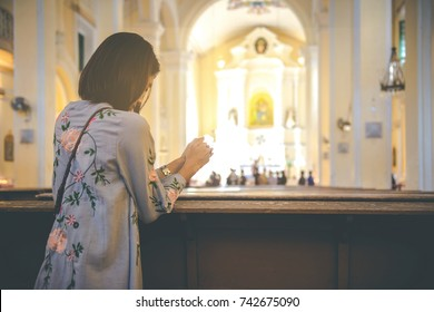 Christian woman is holding hands together and praying in the church, Worship god with christian concept religion.