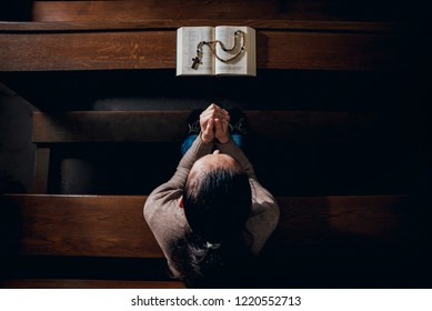 Christian woman praying in church. Hands crossed and Holy Bible on wooden desk. Background