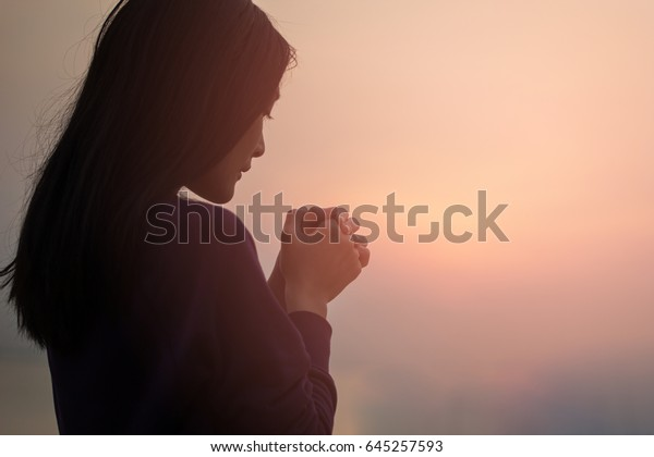 Christian woman praying worship at sunset. Hands folded in prayer. worship god with christian concept religion.