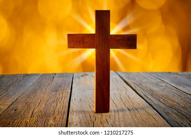 Christian wood cross on blur flare lights and wooden background