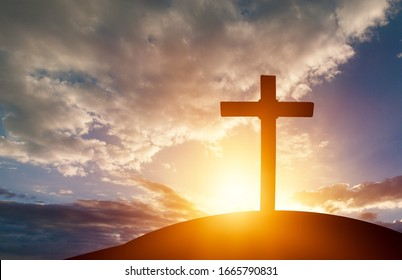 Christian wooden cross on the hill on sunset background