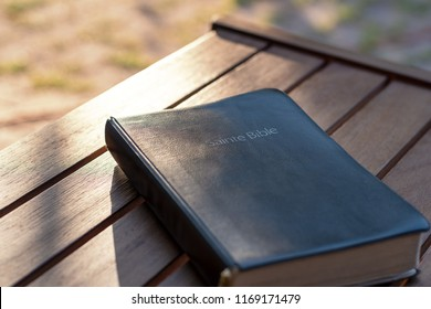 Christian worship and praise. The bible on a chair in the morning light. Text : Holy Bible (in French)