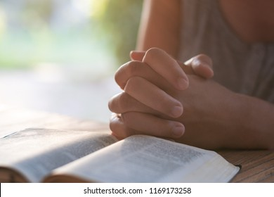 Christian worship and praise. Hands of a young woman on an open Bible in the early morning
