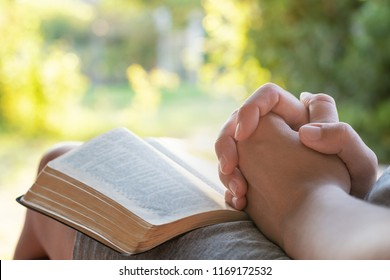 Christian worship and praise. A young woman is reading the Bible in the early morning