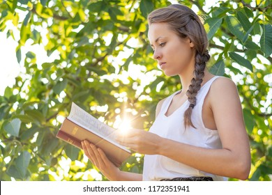 Christian worship and praise. A young woman is reading the bible in the early morning with sun in the background.